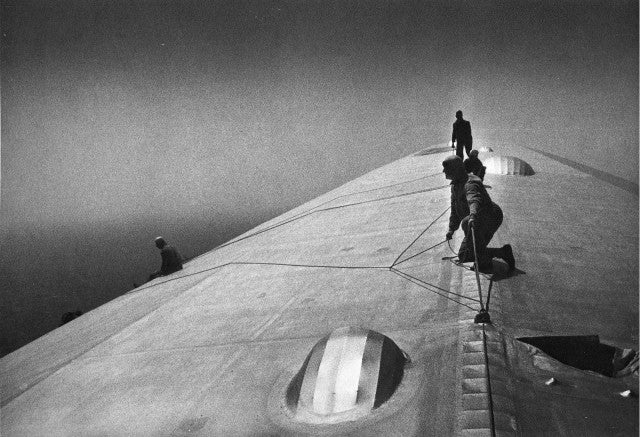 Daredevil men fixing a zeppelin in mid-flight over the Atlantic
