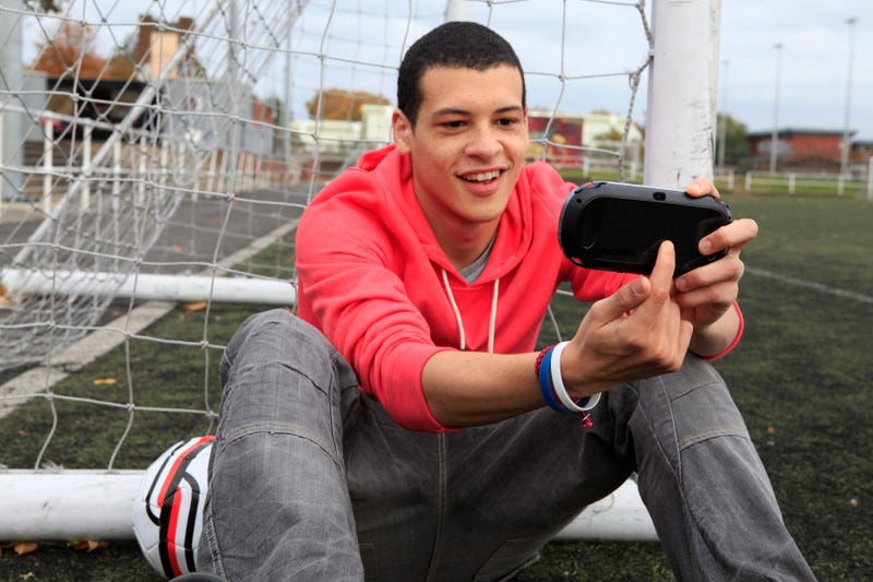 Attractive Young Men Smiling at the PlayStation Vita