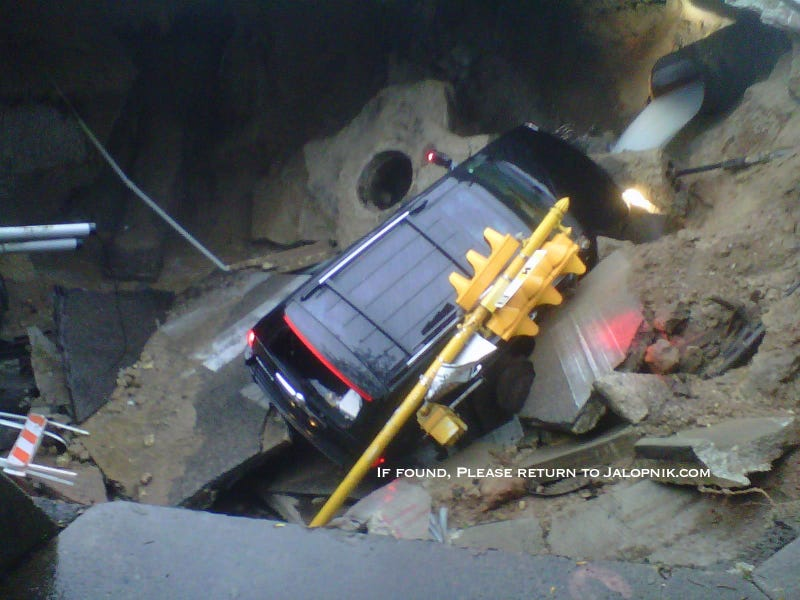 Milwaukee Sinkhole Swallows Cadillac Escalade, Traffic Light