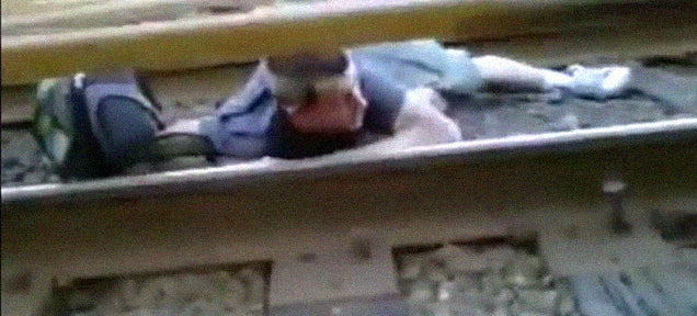 Crazy kid crawls across the railway tracks under a running train