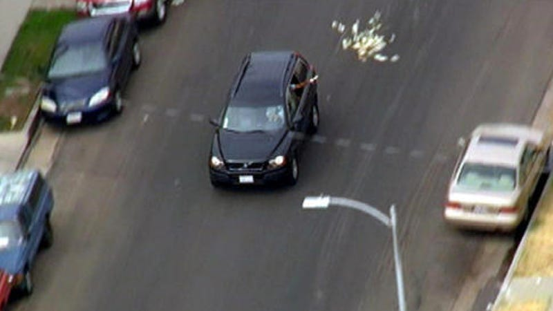 A Man Is Throwing Money Out Of His Car During A California Car Chase