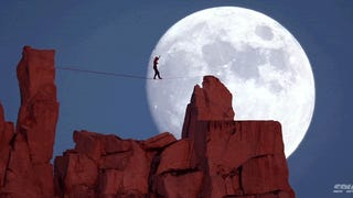 Guy walking on a tight rope against a beautiful giant moon