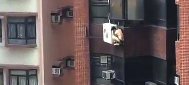 Why is this naked guy clinging to an eighth floor air conditioner?