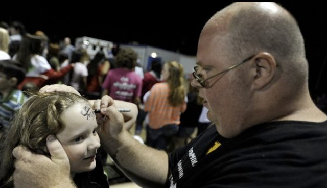 Presenting A Picture Of Chad McGhee Signing A Young Knox City Greyhounds Fan's Forehead