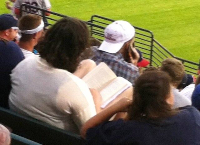 Yet Another Photo Of Someone Reading At A Baseball Game