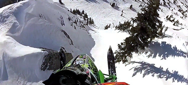 Watch this snowmobile launch off a cliff and feel your stomach drop