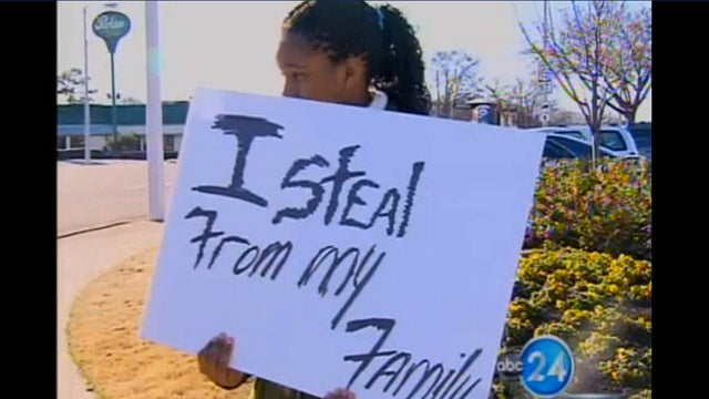 Teen Girl Forced to Stand on Busy Corner Holding an 'I Steal From My Family' Sign