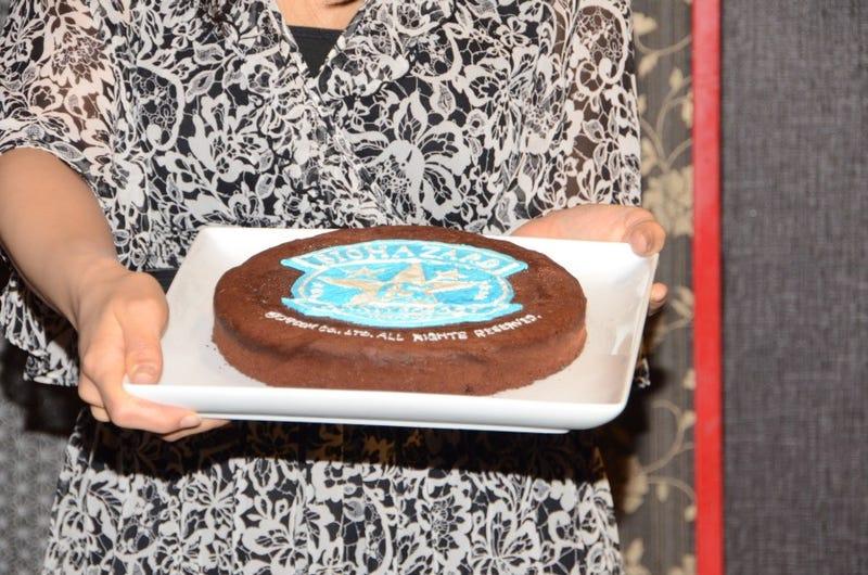 A Lady Holds a Resident Evil Pistol. Capcom Copyrights a Cake.
