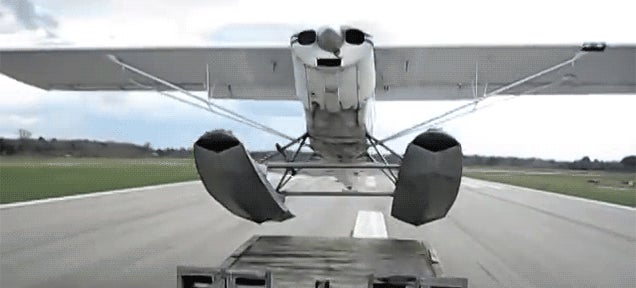 Daredevil seaplane pilot takes off from a towed truck trailer