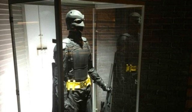 A Celebration of Superheroes Staring at Costumes in Fancy Display Cases