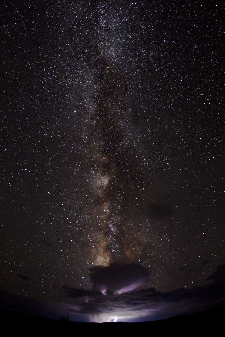 An incredible view of the Milky Way stretched above a distant monsoon