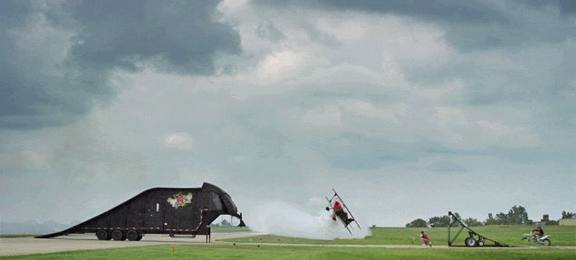 Motorcycle jumps over plane that's flying sideways close to the ground