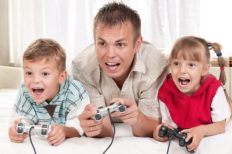 A Dad And His Kids Happily Play Video Games Together. They Have To.