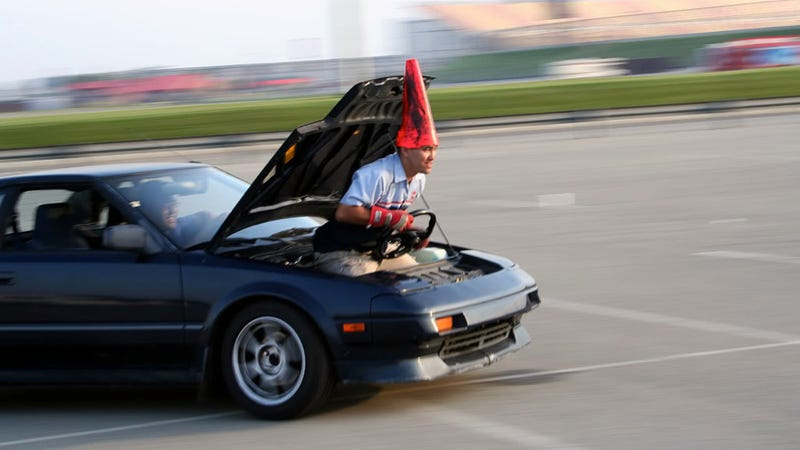 Here's A Guy Riding In The Trunk Of An Autocross MR2 Wearing A Cone For A Helmet
