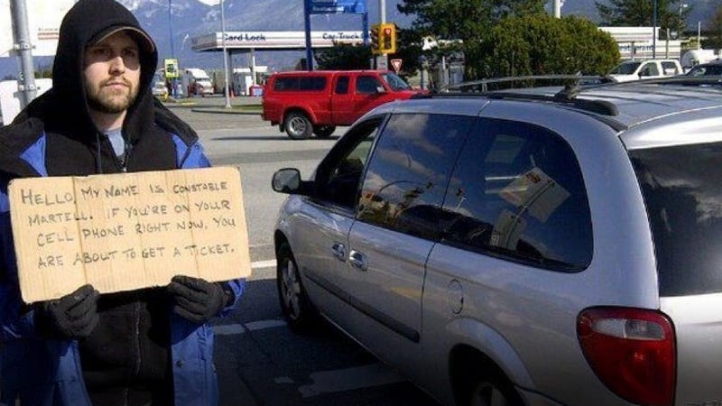 This Bum With A Sign Is Really A Sneaky Ticket-Writing Cop In Disguise