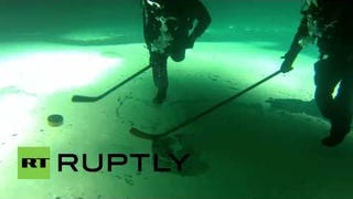 Two Men Play An Upside-Down Game Of Ice Hockey, UNDERWATER