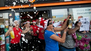 "[Workers of a gas station celebrate with friends and clients after winning the second prize of the Christmas lottery ""El Gordo"" (""The Fat One"") in Spain. Photo by Andres Gutierrez via AP]"