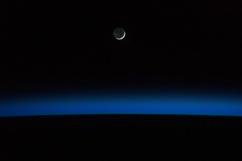 A Crescent Moon Above a Darkened Planet