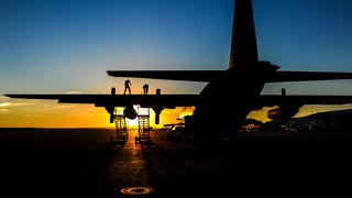 A spectral sunset over a creepy war plane. Airmen from the 1st Special Operations Aircraft Maintenance Squadron work on an AC-130U Spooky Gunship at Marine Corps Air Station Miramar in California on November 3rd. [Senior Airman Christopher Callaway/U.S. Air Force]