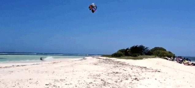 Watch this guy jump over an entire island while kitesurfing