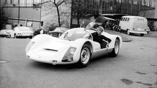 [A lady moves a Porsche 906 Carrera 6 at Zuffenhausen, 1966. The 906 was the last street-legal race car Porsche made, and the first of its race cars to be tested in a wind tunnel. Photo credit: Porsche]
