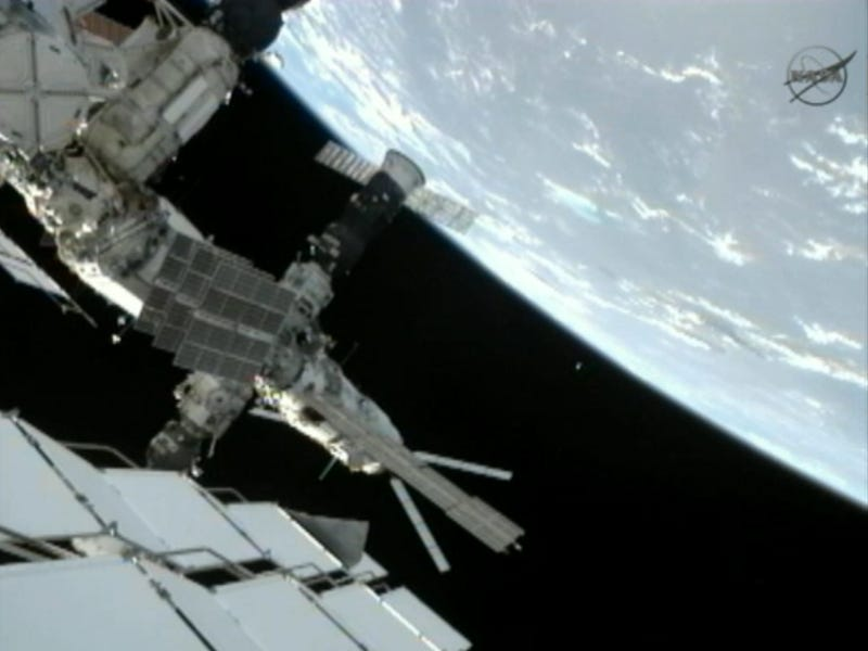 Spacewalking cosmonauts heave a 20-pound metal ball into Earth orbit