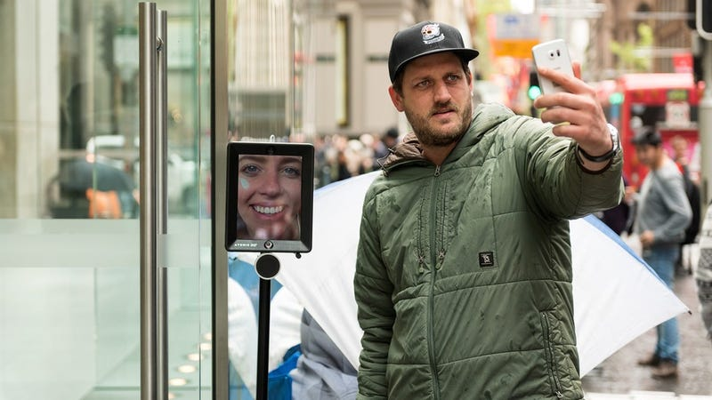 Una mujer hace cola para comprar el iPhone 6s mediante un robot de telepresencia
