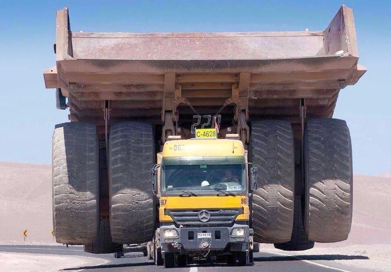 Trailer truck dwarfed by its massive mining truck cargo