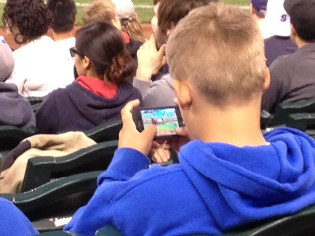 Bored Baseball Fans Play Baseball Video Games At Baseball Game