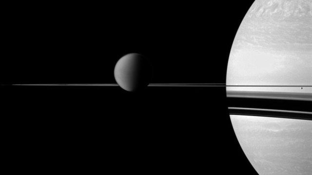 The moon Titan rests on Saturn's razor-thin rings