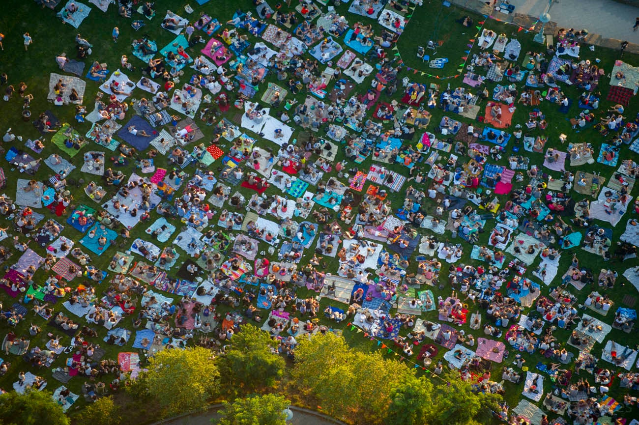 Aerial photo of a sea of people having a picnic in a park
