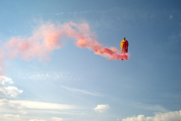 Smoke-bending artist flies through the air on a bright pink cloud