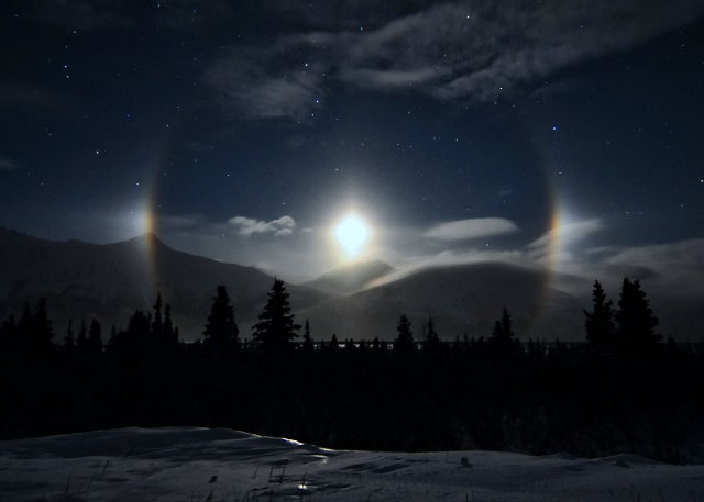 A ring of illuminated ice crystals encircle an Alaskan moon
