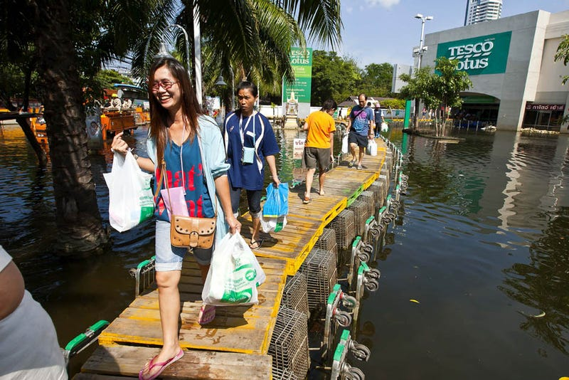 Faced with rising floodwaters, Thai citizens turn to homemade jet skis and abandoned highway parking lots