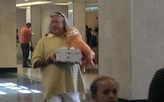 Rob Ryan Saunters Around Airport With Three Pizzas And Plush Animal