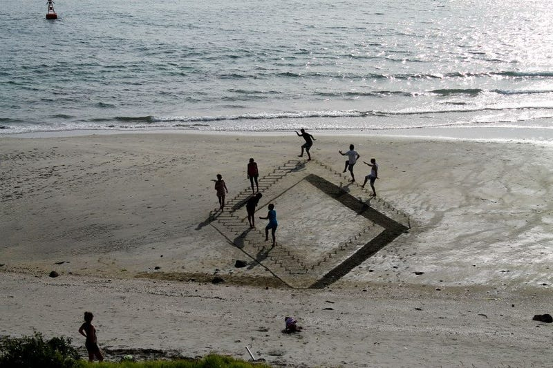 These 3D sand drawings create fun trippy illusions on the beach
