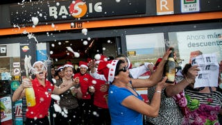 """[Workers of a gas station celebrate with friends and clients after winning the second prize of the Christmas lottery """"El Gordo"""" (""""The Fat One"""") in Spain. Photo by Andres Gutierrez via AP]"""