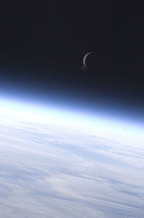 A crescent moon rises above an unearthly sphere