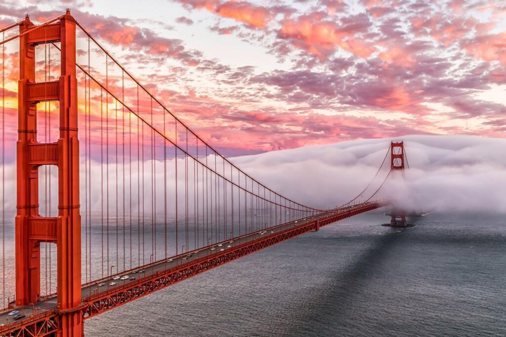 A wall of fog invades the Golden Gate bridge at sunrise