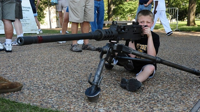 For Some Reason, Adorable Kids Are Holding Big Ass Guns