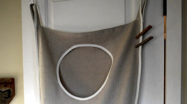 Hang a Laundry Hamper on The Back Of Your Closet Door to Save Space