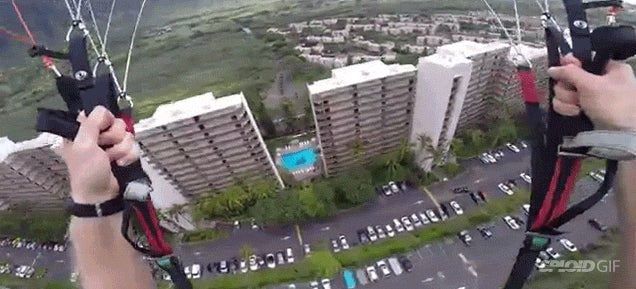 Paraglider daredevil swoops right in between two buildings