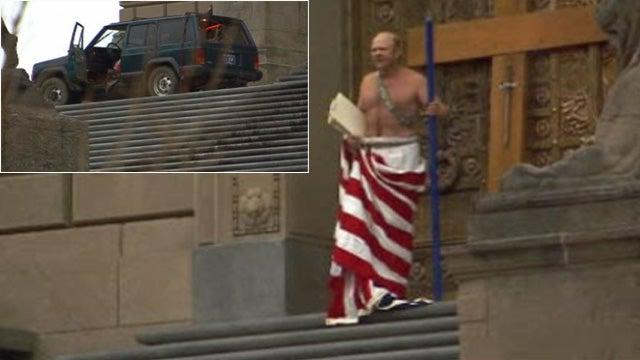 Man Wearing a U.S. Flag Drives Jeep Up War Memorial, Sets It On Fire