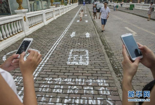 Smartphone Sidewalks Pop Up on a Busy Street in China