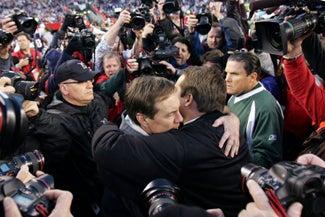 Many People Taking Photos Of Two Men Hugging