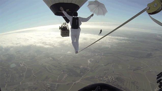 Insane people walk a line between hot air balloons above the clouds