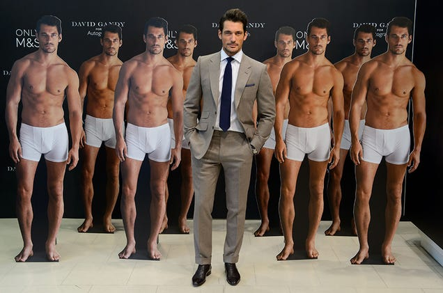Model David Gandy poses with cardboard cutouts of himself wearing underwear from his new collection