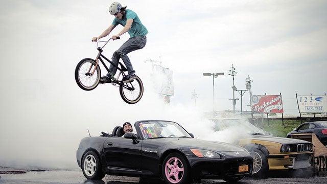 Watch a bike jump a GT-R-powered BMW doing a burnout