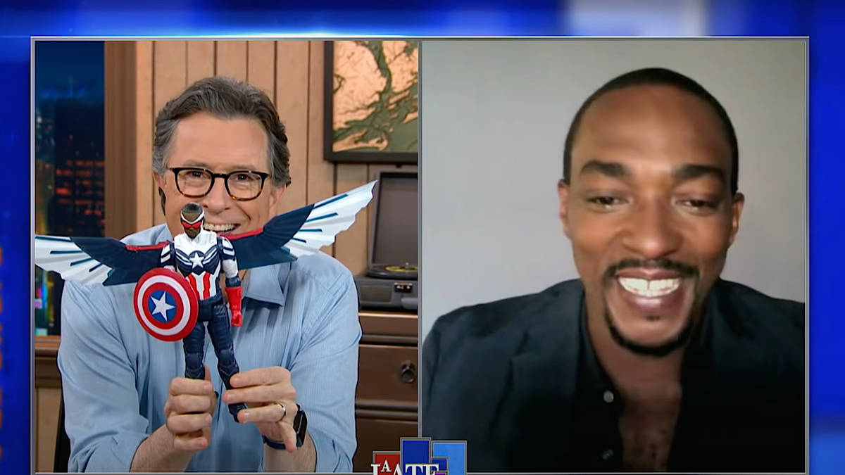 Stephen Colbert shows off his pre-release Captain America doll to an envious Anthony Mackie