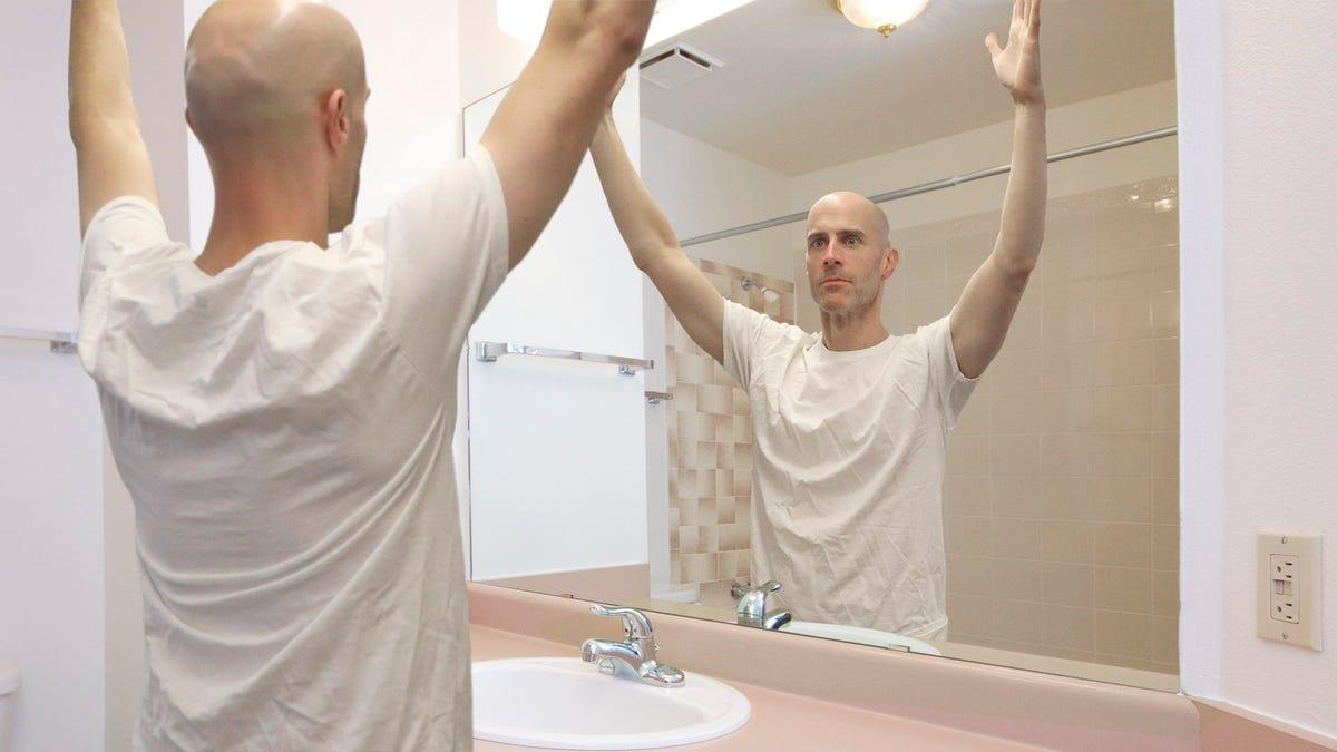 Selbst-Bewusste NFL Schiedsrichter Praktiken Heben Beide Arme Vor dem Badezimmerspiegel Vor dem Spiel